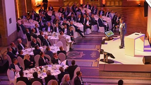 Redner auf der Bühne mit Tischen auf der Abendgala